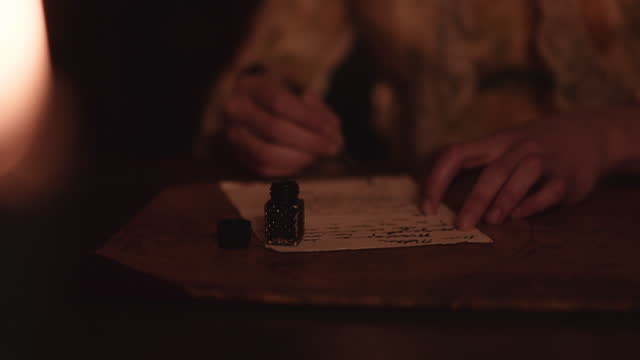 Quill and ink by candle light.