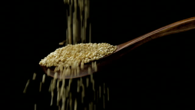 Quinoa seeds Quinoa seeds falls into a wooden spoon spoon stock videos & royalty-free footage