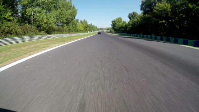 低角度のビュー。レースカー競合とお車で高速のレーストラックラップ - 戦い点の映像素材/bロール