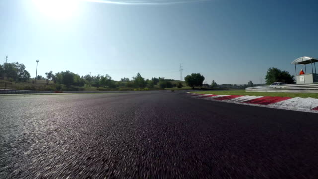 LOW ANGLE VIEW: Race car competing and driving fast on race track lap video