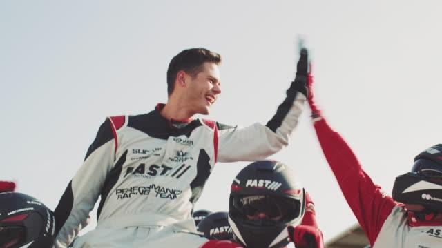 stockvideo's en b-roll-footage met autocoureur vieren van succes met team - winnen
