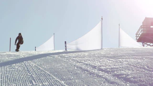 SLOW MOTION: Race snowboarder starts riding slalom between the flags video
