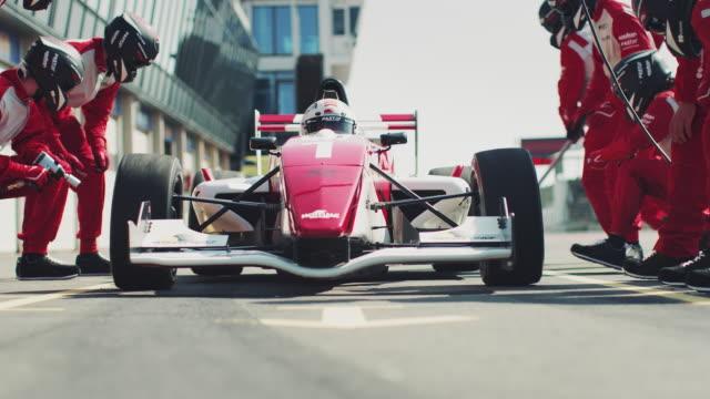 vídeos de stock e filmes b-roll de racecar arriving at pit stop during race - equipa desportiva