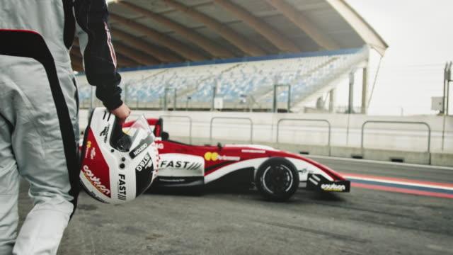racedriver arabasına doğru yürüyor - başlama çizgisi stok videoları ve detay görüntü çekimi