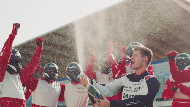 stockvideo's en b-roll-footage met racer en crew leden genieten op sport plaats - winnen