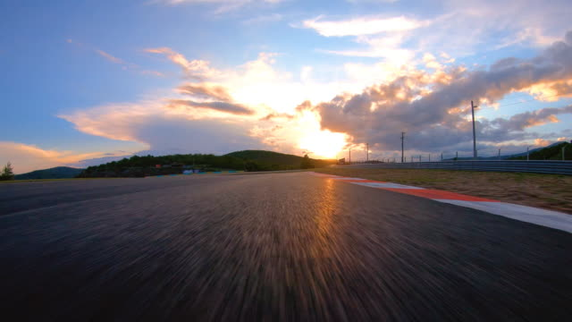 Racing at sunset Driving fast on a race track, illuminated by the light of a setting sun angle stock videos & royalty-free footage