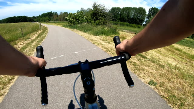 Racing bicycle on small road in the country side Point of view from a man who rides a racing bicycle. He drives on a road and the camera points toward the road. handlebar stock videos & royalty-free footage