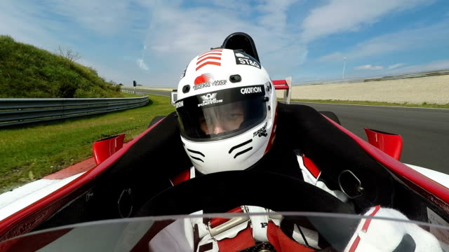 Racing driver in cockpit steering formula one car A professional racedriver is sitting in a cockpit of a formula one car. He is steering on a racetrack. The camera is pointing backwards. crash helmet stock videos & royalty-free footage