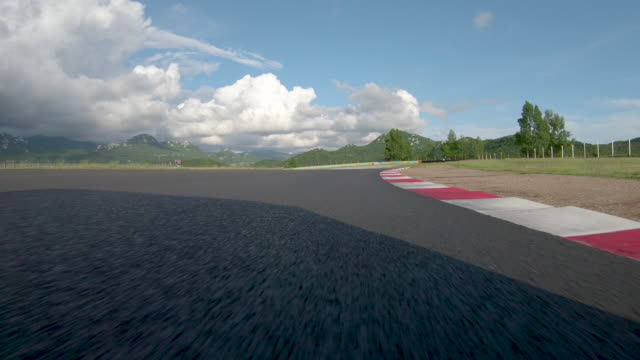 POV: Racing on a closed asphalt racetrack during a track meet on a sunny day.