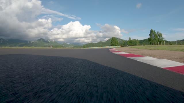 pov: güneşli bir günde bir parça buluşma sırasında kapalı asfalt pist üzerinde yarış. - pist stok videoları ve detay görüntü çekimi