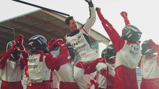 racing team celebrating success at sports venue - campionato video stock e b–roll
