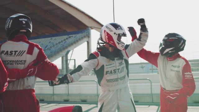 vídeos de stock e filmes b-roll de racing team cheering at sports venue - equipa desportiva