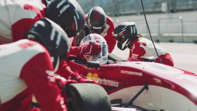 vidéos et rushes de écurie, réparer une voiture de formule 1 à l'arrêt au stand - lieu sportif