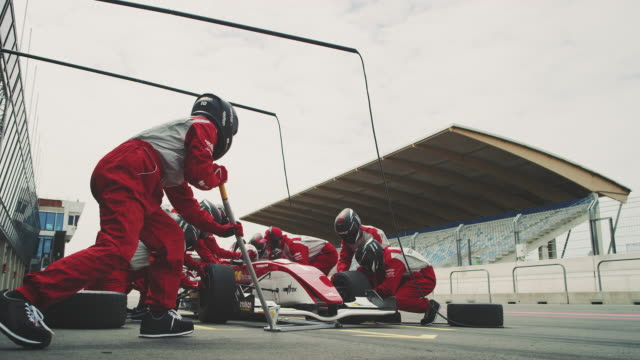 Racing team repairing Formula One car at pit stop