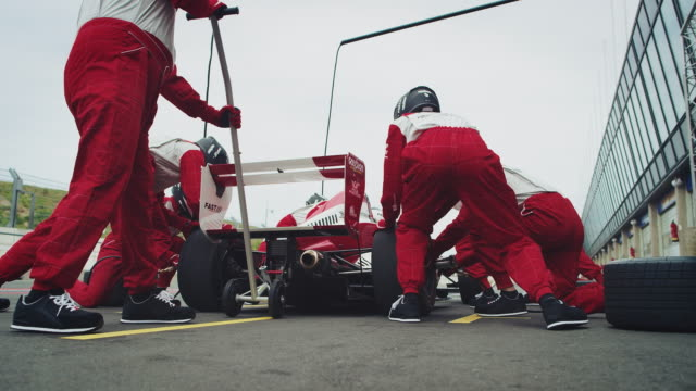 racing team repairing racecar at pit stop - mechanik filmów i materiałów b-roll