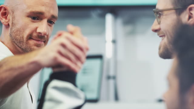 vídeos de stock e filmes b-roll de racing team shaking hands at pit stop - equipa desportiva