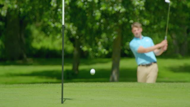 Ein Rack Focus Clip eines Golfers, der einen Schuss aus einer Sandfalle auf das Grün und in der Nähe des Stifts spielt. – Video