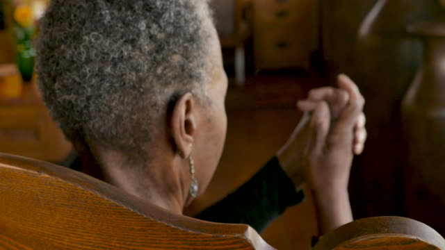 Rack focus of a senior black woman rubbing her hands together