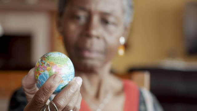 Rack focus of attractive African American senior woman looking at world globe video