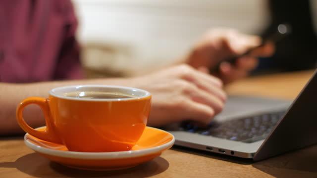노트북의 측면에서 휴대 전화를 사용 하 여 손의 랙 초점 - 초점 이동 스톡 비디오 및 b-롤 화면