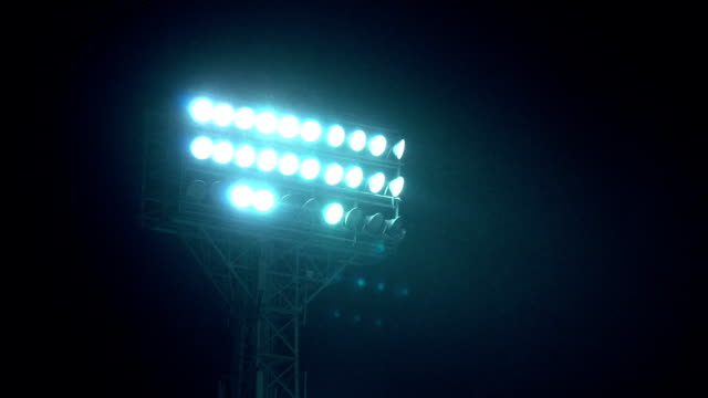 Rack focus of stadium lights in front of a dark blue sky. Rack focus of stadium lights in front of a dark blue sky. Light Stadium at night, baseball and hockey. There is a rain or snow. military security lighting towers, patrol in prison floodlit stock videos & royalty-free footage