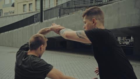 vidéos et rushes de rack focus de deux hommes agressifs se battant dans la rue - arts martiaux