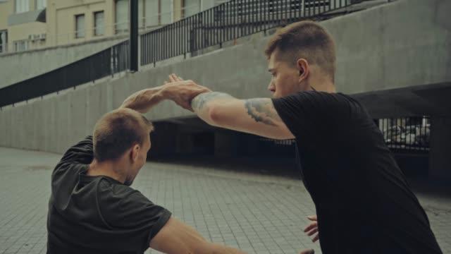 vídeos de stock, filmes e b-roll de foco rack de dois homens agressivos lutando na rua - artes marciais