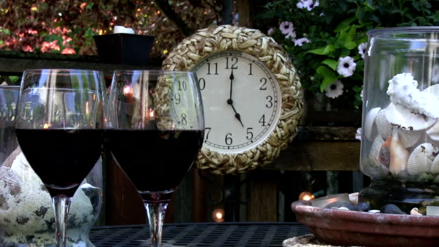 Rack focus of Wine glasses with clock at 5PM outdoors video