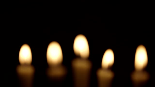Rack focus on lit candles video