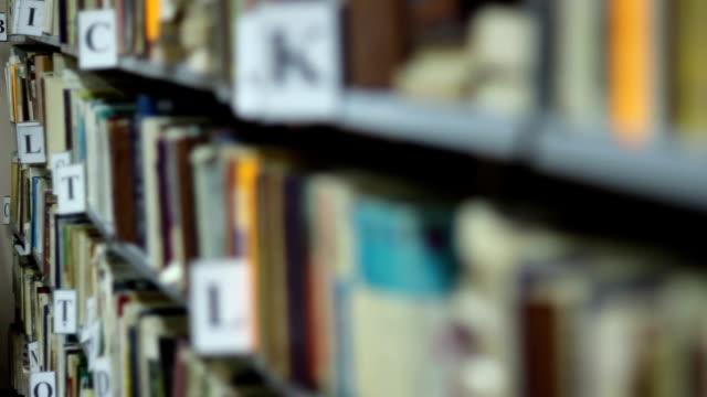 rack focus over bookshelf - looking inside inside cabinet bildbanksvideor och videomaterial från bakom kulisserna