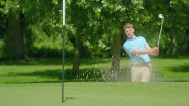 Ein Rack Focus-Schuss eines Golfspielers, der in Zeitlupe einen Schuss aus einer Sandfalle trifft und sich auf den Golfball auf das Grün konzentriert. – Video