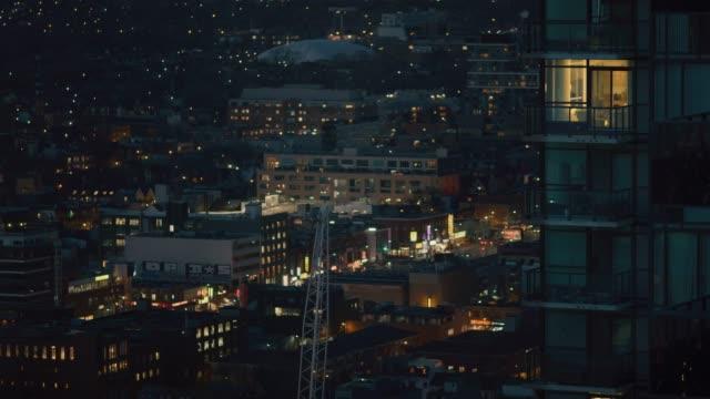 랙 초점에 빛을 가진 아파트입니다. 도시의 반짝 빛 배경에 있습니다. 어두운 밤 풍경입니다. - 초점 이동 스톡 비디오 및 b-롤 화면