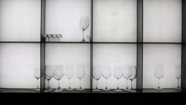 Rack with transparent glasses for various alcohol in the bar. On white background.