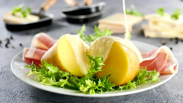 raclette-käse schmelzen auf kartoffel - raclette stock-videos und b-roll-filmmaterial