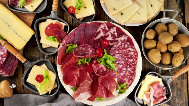 raclette-käse-party mit fleisch, kartoffeln und käse - raclette stock-videos und b-roll-filmmaterial