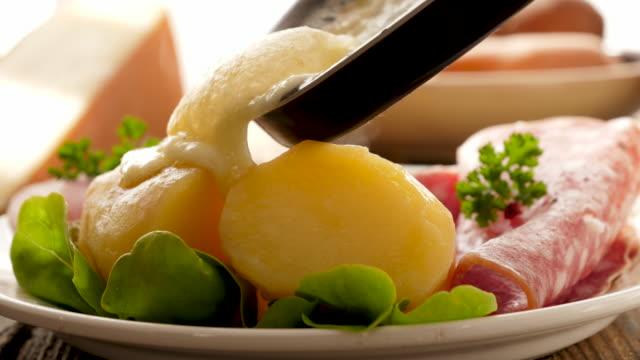 raclette cheese with potato and salami - cucina francese video stock e b–roll