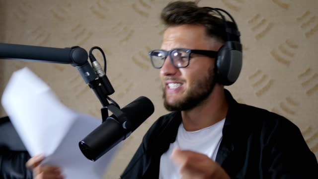 radio presenter in eyeglasses and headset talking into mike and Waving hands at studio video