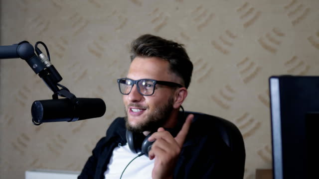 radio presenter in glasses and with headphones talking into microphone in room at work video