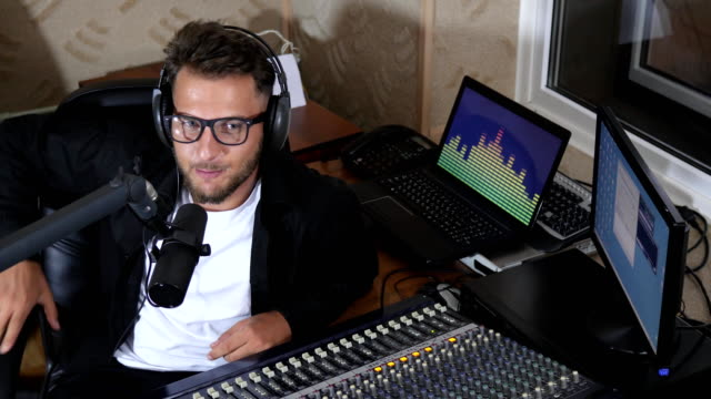 radio presenter into glasses and headphones leads program live on air into microphone, lot of technology and equipment around video