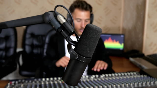 radio station, close-up of professional microphone on background DJ in headphones video