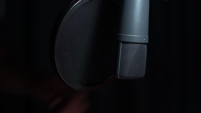 vidéos et rushes de microphone de condensateur de radio studio en cours d'ajustement - interview