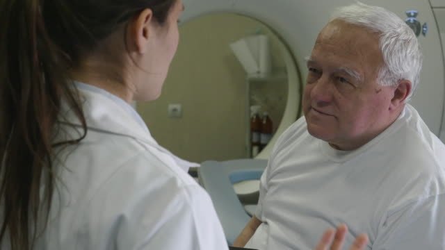 vídeos de stock e filmes b-roll de radiologist preparing the medical scanner for work. talking with the patient and helping him get ready for the procedure. - tomografia