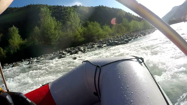 Rafters actively paddling boats, overcoming obstacles on their way, risky sports video
