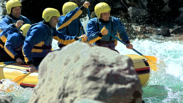 HD SLOW MOTION: Rafters Splashing Through Rapids HD1080p: Slow Motion shot of whitewater rafters splashing through the river rapids while rafting on the rough water. rapids river stock videos & royalty-free footage
