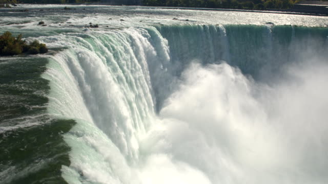 aerial, close up: raging niagara river falling over the edge on horseshoe falls - niagara falls stock videos & royalty-free footage