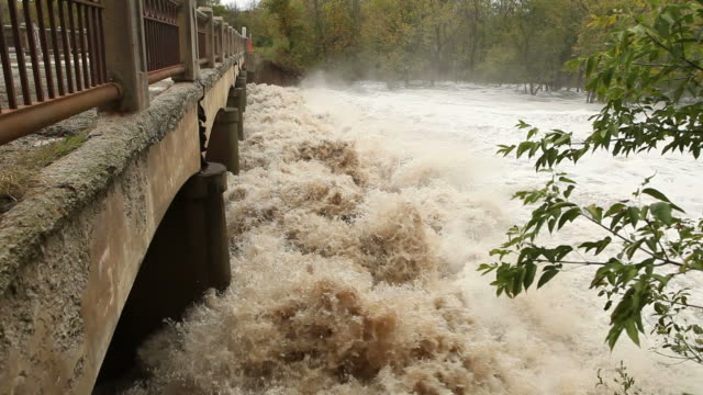 Raging River Floodwater Under a Bridge