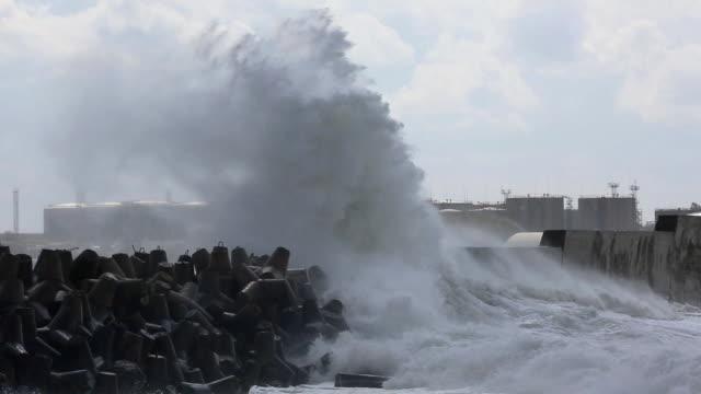 raging storm in harbor with oil tanks - dalgakıran stok videoları ve detay görüntü çekimi