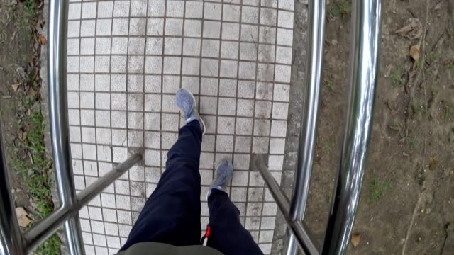 railing of rehabilitation with man's feet in the park.pov - physical therapy стоковые видео и кадры b-roll
