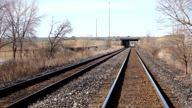 Railroad tracks going under highway in the spring