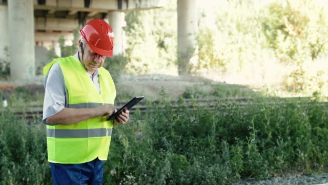Railroader fixing data on the tablet when checking a serviceability of railway video